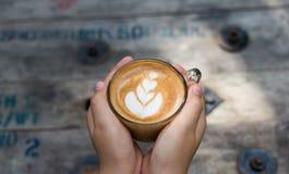 拿着一杯咖啡在木桌,顶视图的女性手 库存照片