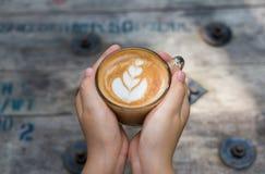 拿着一杯咖啡在木桌,顶视图的女性手 免版税库存照片
