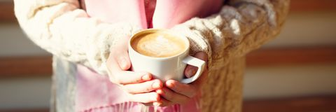 拿着一杯咖啡或热巧克力或者柴茶拿铁的女孩 免版税库存照片