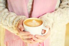 拿着一杯咖啡或热巧克力或者柴茶拿铁的女孩 库存图片