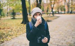 拿着一杯咖啡拿铁的外套的妇女用牛奶 多雪的秋天的偏僻的立场在公园离开了街道 图库摄影