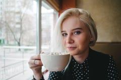 拿着一杯咖啡的一个年轻美丽的白肤金发的女孩的画象用蛋白软糖手中 库存照片