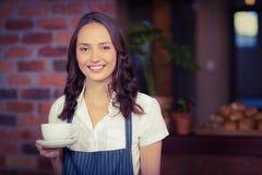 拿着一杯咖啡的俏丽的女服务员 免版税库存图片