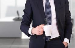 拿着一杯咖啡的商人。 库存图片