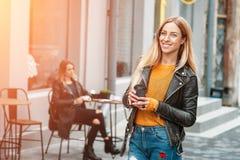 拿着一杯咖啡的太阳镜的美丽的年轻白肤金发的时髦的妇女,当站立室外时 免版税库存图片