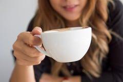 拿着一杯咖啡的微笑的美丽的亚裔女孩 图库摄影
