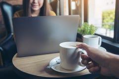 拿着一杯咖啡的手喝与工作和键入在膝上型计算机键盘的一名美丽的亚裔妇女在背景中 免版税库存图片