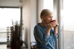 拿着一杯咖啡的窗口的资深妇女 图库摄影