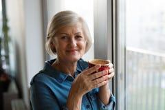 拿着一杯咖啡的窗口的资深妇女 库存照片