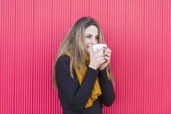 拿着一杯咖啡的美丽的少妇 红色背景 L 图库摄影