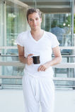 拿着一杯咖啡的年轻成人 图库摄影