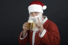 拿着一杯啤酒的圣诞老人。 免版税图库摄影