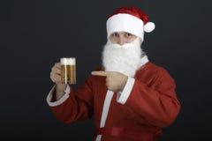 拿着一杯啤酒的圣诞老人。 免版税库存照片