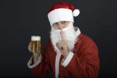 拿着一杯啤酒的圣诞老人。 库存图片