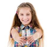 拿着一杯在她前面的水的逗人喜爱的女孩 免版税库存图片