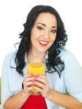 拿着一杯新鲜的橙汁的健康愉快的少妇 库存图片
