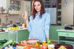 拿着一杯汁液,微笑的俏丽的妇女,看照相机、常设桌用新鲜的水果和蔬菜o 图库摄影