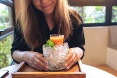拿着一杯混杂的桔子和红萝卜汁的妇女在一个瓶子冰与薄荷叶在咖啡馆 免版税库存图片