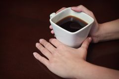拿着一杯温暖的咖啡的2只手 免版税库存照片