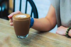 拿着一杯热巧克力的妇女手,在与心形的牛奶泡沫的一块玻璃 免版税库存图片
