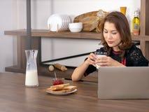 拿着一杯牛奶的亚裔美女使用膝上型计算机 免版税库存照片