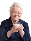 拿着一杯牛奶的健康老妇人 免版税库存照片