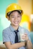 拿着一杯牛奶的年轻亚裔孩子 库存照片