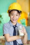 拿着一杯牛奶的年轻亚裔孩子 免版税图库摄影
