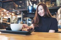 拿着一杯白色咖啡在木桌上的妇女的特写镜头图象 库存照片