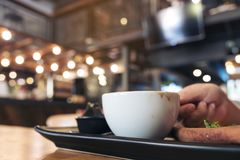 拿着一杯白色咖啡在黑茶碟的妇女的特写镜头图象在木桌上 免版税库存照片