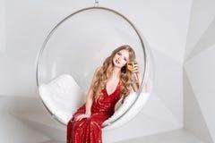 拿着一杯白葡萄酒的红色礼服的年轻白肤金发的妇女坐在透明椅子对有几何的墙壁 库存照片