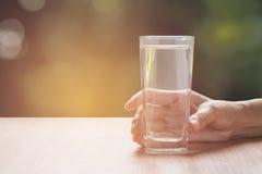拿着一杯纯净的水的手 玻璃现有量藏品 免版税库存图片