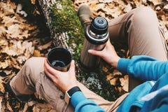 拿着一杯茶和热水瓶的旅客妇女在秋天森林里 免版税库存图片