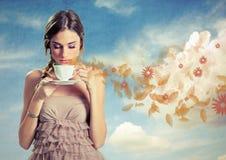 拿着一杯茶在天空背景的美丽的少妇 免版税库存图片