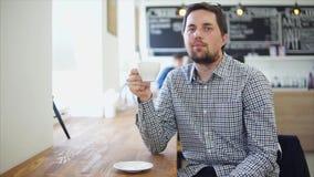 拿着一杯茶或咖啡的一个年轻人的画象在他的手上在咖啡馆 股票视频