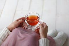 拿着一杯茶的一只灰色毛线衣和温暖的袜子的妇女,当坐白色编织了毯子时 图库摄影