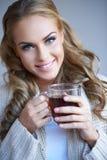 拿着一杯茶的一名俏丽的妇女的特写镜头 免版税库存图片