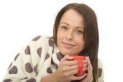 拿着一杯茶的可爱的轻松的愉快的舒适少妇 库存图片