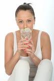 拿着一杯被冰的水的健康可爱的少妇 免版税库存照片