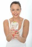 拿着一杯被冰的水的健康可爱的少妇 库存图片