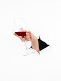 拿着杯酒的女性手 免版税库存图片