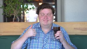 拿着一杯饮料可乐和显示赞许姿态的肥胖愉快的人,坐在咖啡馆 打赌的人 股票视频