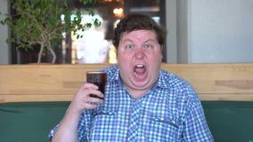 拿着一杯饮料可乐的恐慌的肥胖人是叫喊的在愤怒,坐在咖啡馆 打赌的人 股票录像