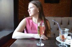 拿着一杯香槟或酒,饮用的香槟的美丽的白肤金发的女孩在一家餐馆,一件平衡的桃红色礼服的 免版税库存图片