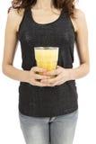 拿着一杯香蕉圆滑的人的妇女 免版税图库摄影