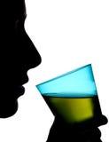 拿着一杯绿色饮料的妇女的剪影 库存图片