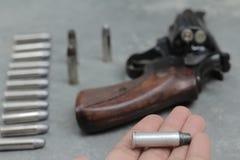 拿着一枚子弹并且开枪迷离 库存图片