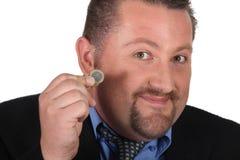 拿着一枚欧洲硬币的人 免版税图库摄影