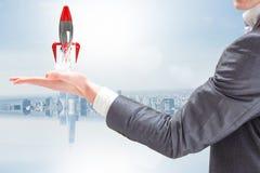 拿着一枚火箭离开从他的手的商人反对蓝色背景 免版税库存图片