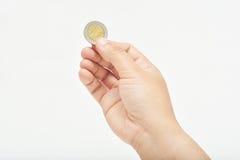拿着一枚硬币的手 免版税库存照片